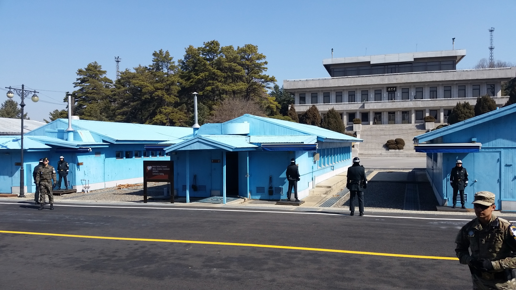 Building T-2, centered, at Panmunjom. Buildings T-1, T-2, and T-3 are visible in the picture as blue buildings in the foreground. In the background is North Korea's large building at Panmunjom.