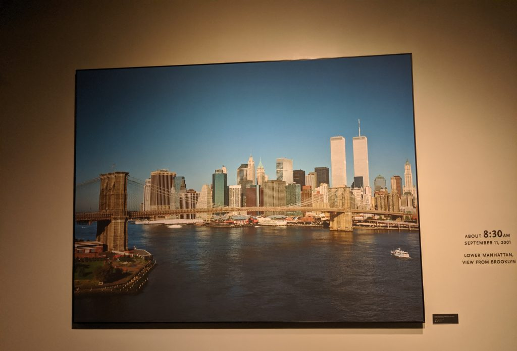 "A photograph taken the morning of September 11, before the planes reached New York.  The legend next to the photograph reads ""About 8:30 AM September 11, 2001 Lower Manhattan, view from Brooklyn."""