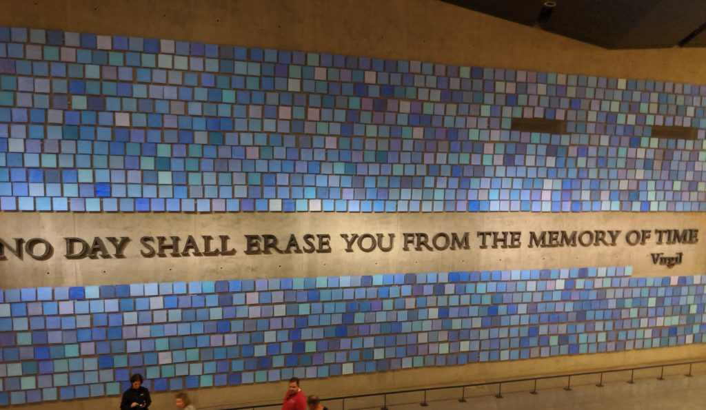 "A large memorial on the wall.  Large text in the middle reads ""No day shall erase you from the memory of time - Virgil"" and is surrounded by many different blue squares.  The hue of each square is supposed to represent the color of the sky as remembered by a different person."