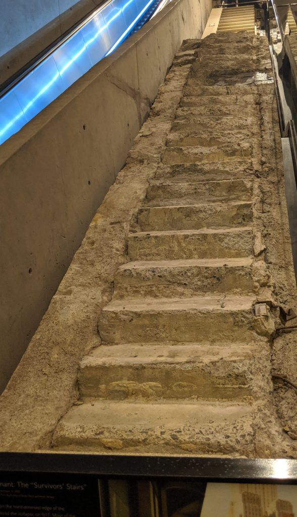 "The ""Survivors' Stairs,"" used by a significant number of victims to escape.  Image depicts a concrete staircase where the bottom portion is significantly damaged."
