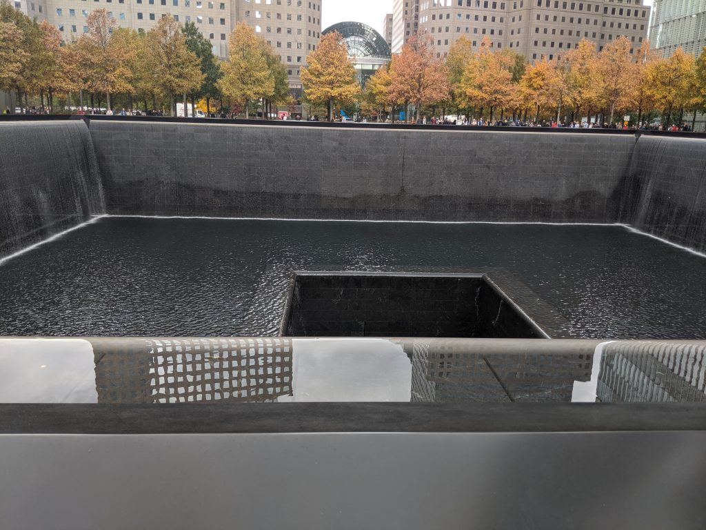 A picture depicting one of the fountains at the 9/11 memorial.  The picture is taken at street level and looks down into the fountain.  The fountain is square in the shape of the building.  In the center of the fountain is another square which is deeper and the bottom cannot be seen.  Water flows from the first square into the deeper one.